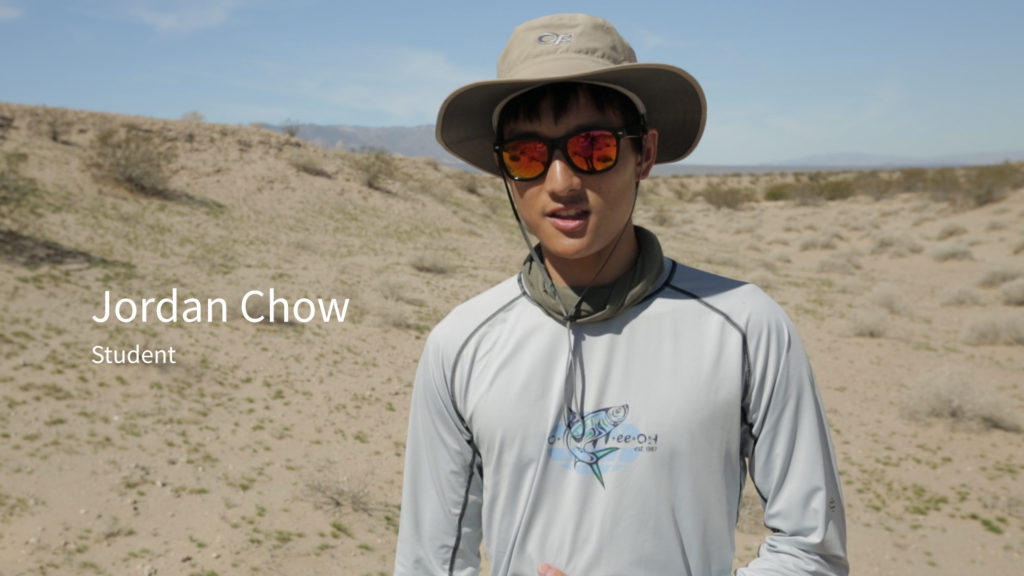 Screenshot of a video showing a student in the desert with his name directly to the left of his image, Jordan Chow. A descriptor--student--is directly beneath his name in smaller font.